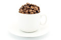 Cup on a saucer filled with coffee beans isolated on white Royalty Free Stock Photo