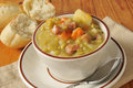 Cup of split pea soup a with a dinner roll Stock Photo