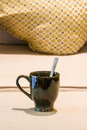 Cup and spoon of tea with inside on sofa Royalty Free Stock Image