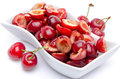 Cup of tasty pitted cherries with whole cherries isolated on white Royalty Free Stock Photos