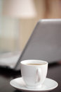 Cup of tea against a laptop Stock Images