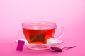 Cup with tea bag on saucer pink background Stock Photography