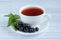 Cup of tea and black currant on a wooden background. Royalty Free Stock Photo