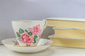 Cup of tea in a china cup and saucer and stack of books Royalty Free Stock Photo