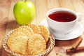 Cup of tea with cookies and apple green on wooden table Stock Photo