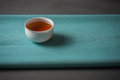 Cup of tea on cotton napkin black in small white porcelain green blue natural Stock Photography