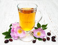 Cup of tea and dogrose on a old wooden background Royalty Free Stock Photos