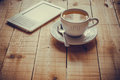 A cup of tea and an ebook reader on a wood table Royalty Free Stock Photo
