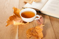 A cup of tea with falling autumn leaves of maple on the background of the wood table