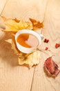 A cup of tea with falling autumn leaves of maple, and a berries of rowan on the background of the wood table