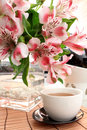 Cup of tea and flowers in a vase Stock Photography
