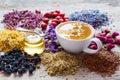 Cup of tea, honey jar, healing herbs and herbal tea assortment Royalty Free Stock Photo
