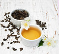 Cup of tea with jasmine flowers on a wooden background Royalty Free Stock Image