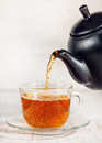Cup of tea with pouring tea and black teapot Royalty Free Stock Photo