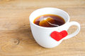 Cup of tea with red heart white shaped label on teabag on wooden background surface love and care concept Royalty Free Stock Photo
