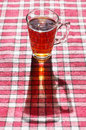 Cup tea red tablecloth bright sunlight Stock Photo