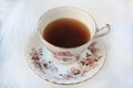Cup of tea in a rose patterned china teacup and saucer Royalty Free Stock Photo