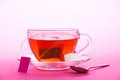 Cup of tea on saucer and sugar slices a a teaspoon a pink background Royalty Free Stock Photo