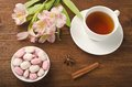 Cup of tea with sweets and flowers Royalty Free Stock Image