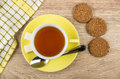 Cup of tea, teaspoon, lumpy sugar on saucer, biscuits Royalty Free Stock Photo