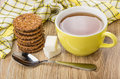 Cup of tea, teaspoon, lumpy sugar, stack of biscuits Royalty Free Stock Photo