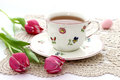 Cup of tea and tulips on beautiful napkin knitted Stock Photography