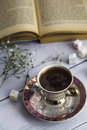 Cup of Turkish coffee with Turkish delights and heart shaped chocolate next to the old book Royalty Free Stock Photo