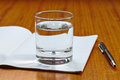 Cup of water and note book pen on the table Royalty Free Stock Photography
