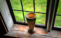 Cup of wood with stem in the windowsill on farm museum sweden Stock Photography