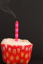 Cupcake with blown out candle on a black background Royalty Free Stock Image