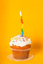 Cupcake with candle one burning on yellow napkin Stock Photo
