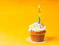 Cupcake with candle one burning on yellow napkin copy space Stock Photos