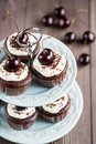 Cupcake chocolate cupcakes with cherries on a plate on wooden background Royalty Free Stock Images