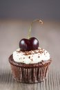 Cupcake chocolate cupcakes with cherries on a plate on wooden background Stock Photos
