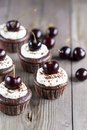 Cupcake chocolate cupcakes with cherries on wooden background Stock Photography