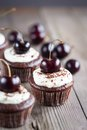 Cupcake chocolate cupcakes with cherries on wooden background Royalty Free Stock Image
