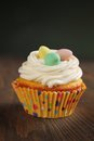 Cupcake with colored eggs on top on a wooden table Stock Photo