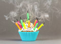Cupcake with colorful candles on grey background Royalty Free Stock Image