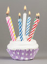 Cupcake with colorful candles on grey background Royalty Free Stock Photos