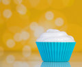 Cupcake with cream butter on yellow background Stock Image