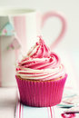Cupcake decorated with a swirl of strawberry and vanilla frosting Stock Image