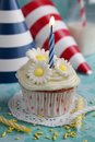 Cupcake with flowers daisy on top and birthday hats in background Royalty Free Stock Photo