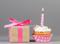 Cupcake with gift box birthday candle and on grey background Royalty Free Stock Images