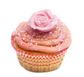 Cupcake with pink flower decoration against white background Stock Images