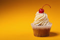 Cupcake with red cherry isolated on orange background with copyspace Stock Photos