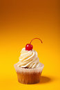 Cupcake with red cherry isolated on orange background with copyspace Stock Photo
