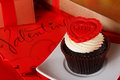 Cupcake with a red heart on top and gifts in boxes on red satin Stock Photo