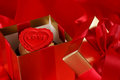 Cupcake with a red heart on top in gifts boxes on red satin back Royalty Free Stock Photos
