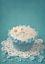 Cupcake with white and blue flowers on background Stock Photo