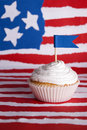 Cupcake with white topping on an american flag background Stock Images